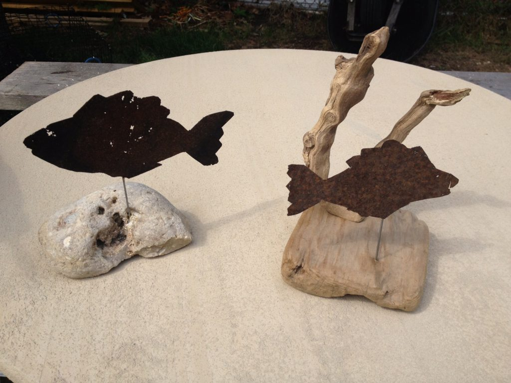 Recycled metal, driftwood, beach rock.